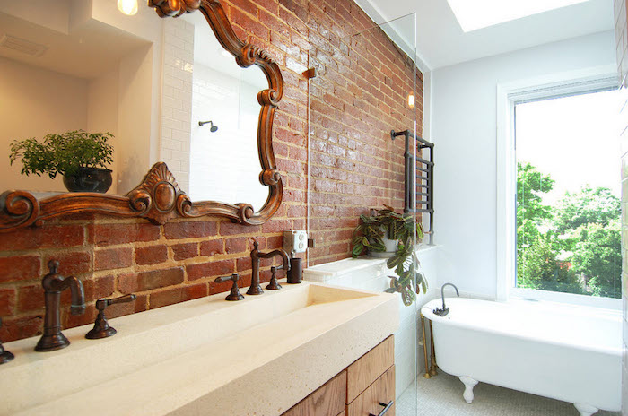 brickwork wall with a large mirror, in an antique ornate frame, a clawfoot bathtub, and the sink with two antique faucets, bathroom wall decor ideas, large window and potted plants