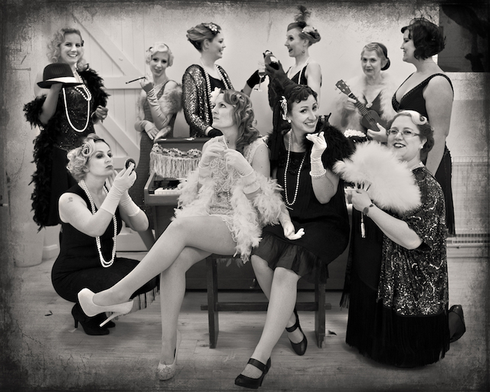 greyscale faux vintage photo, showing a group of women, all dressed in gatsby inspired dresses, with feather boas, long pearl necklaces, smiling and posing for the camera