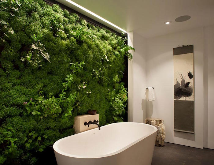 ferns and moss, and other green plants, entirely covering a wall, near a white round bathtub, nice bathrooms, the rest of the walls are white, and the floor is beige