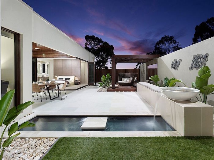 postmodern building in white, with a rectangular pool, and a dark brown wooden gazebo, backyards with pools, a small patch of grass