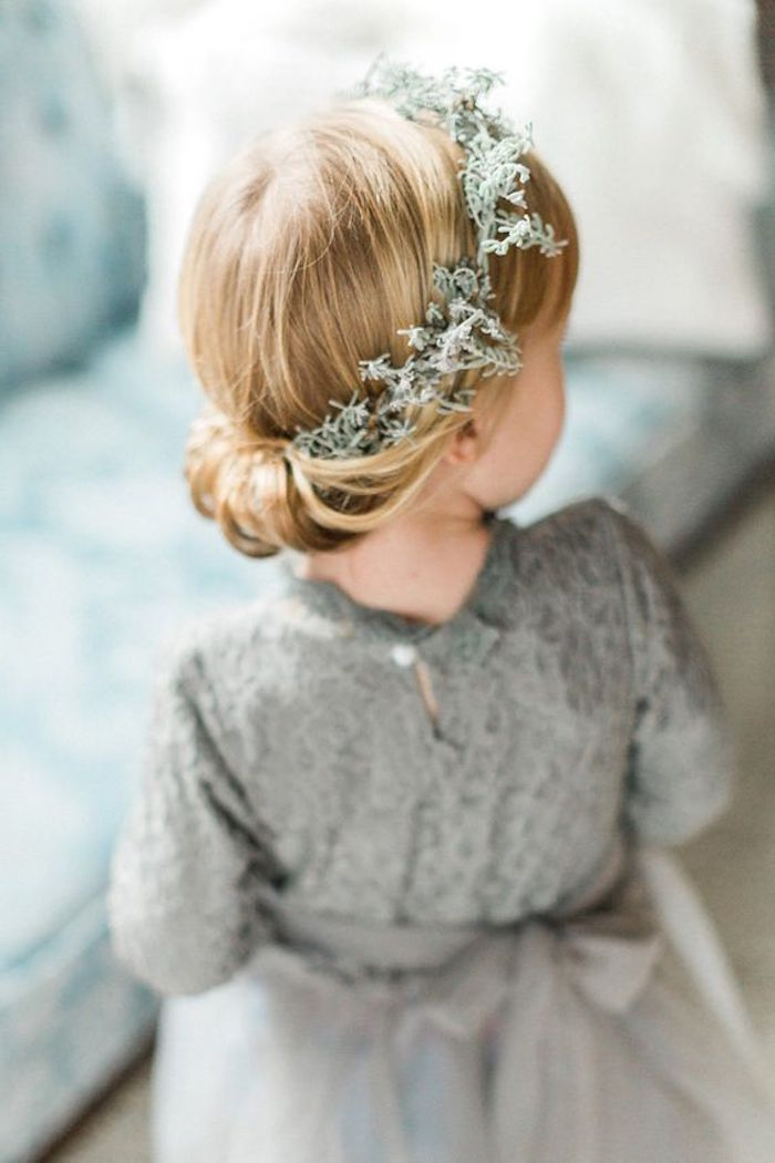 creamy grey formal dress, worn by a little blonde girl, with an up-do, simple hairstyles, braided around a moss-like, pale green wreath