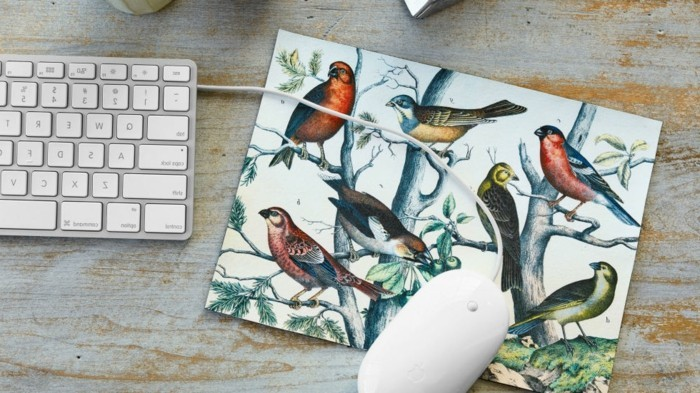 drawings of birds and trees, decorating a mousepad, with a white mouse, near a keyboard