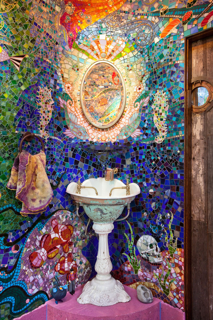 mosaic in many different colours, with fish and other sea creatures, bathroom wall decor ideas, antique style sink, pink floor and a wooden door