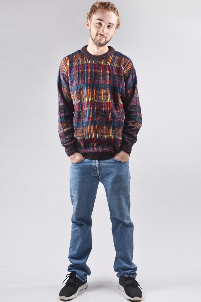 smiling young man, with short mustache and beard, wearing a long, multicolored sweater, black sneakers and baggy jeans