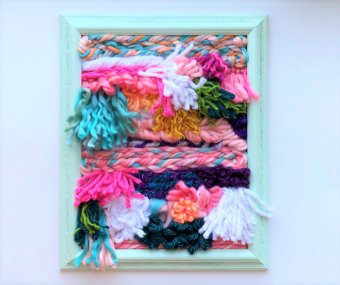 diy gifts for friends, colorful yarn in different shapes, inside a wooden turquoise frame, mounted on white wall