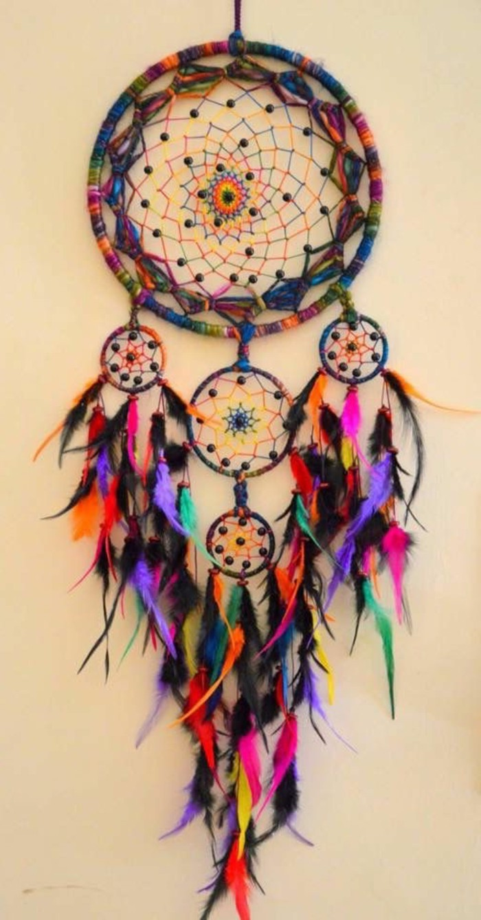 bright boho-style large dream catcher, with one big and four small, multicolored nets, featuring small feathers, in different colors