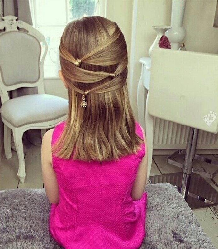 fuchsia pink formal sleeveless dress, worn by a young girl, with wavy honey blonde hair, decorated with knotted details, girl haircuts, medium length style