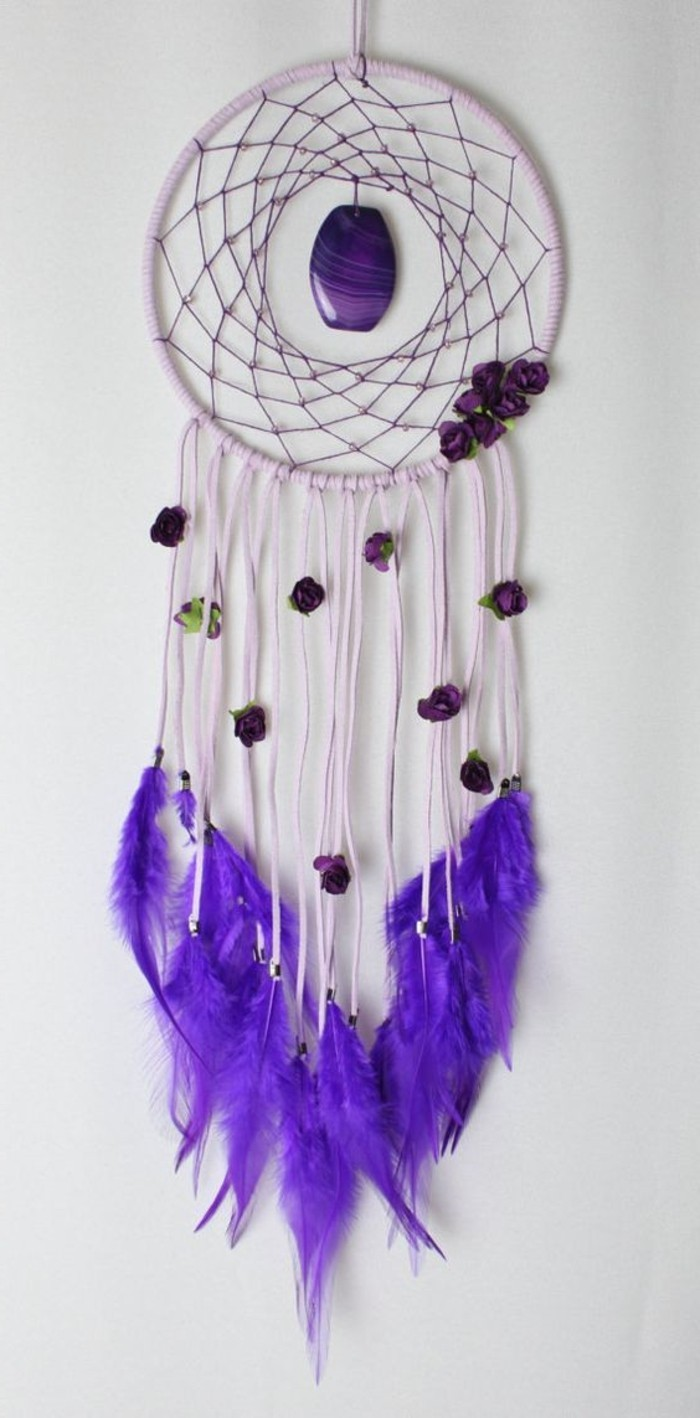 stine in purple, decorating a pale purple dreamcatcher, with long tassels, and neon violet feathers