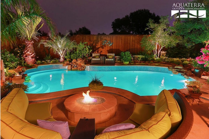 fire pit surrounded by yellow sofas, in a garden with a turquoise pool, palm trees and flowers, photo taken at night