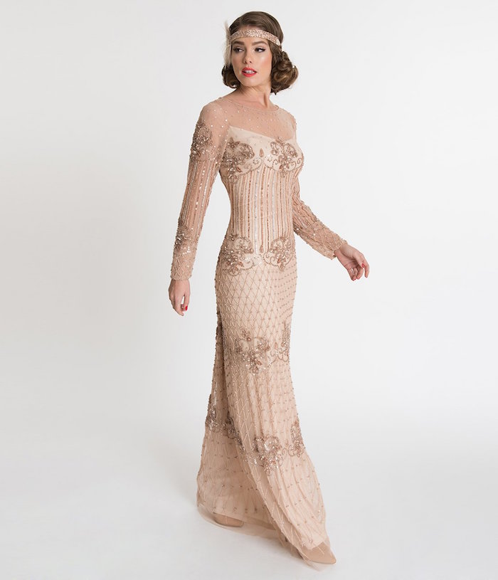 maxi dress in nude pink, with sheer sleeves, and gold embroidery, featuring art deco motifs and beads, worn by slim brunette woman, with a matching pink headband