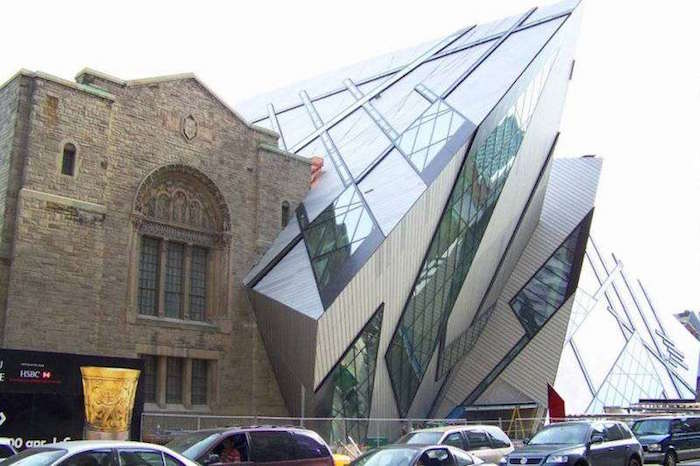 jagged glass and metal structure, fused with an old building, made from beige bricks or stone, and featuring ornate widnows
