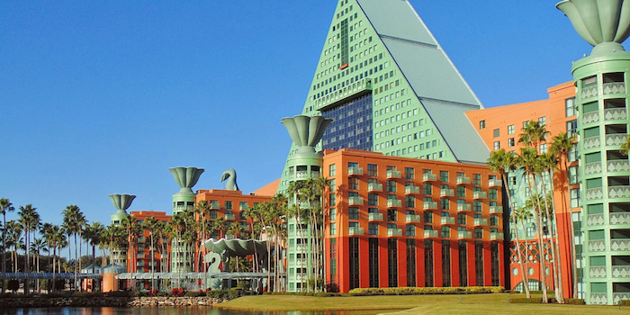 modernism and postmodernism, disney resort's swan hotel, in yellow and green, with a pyramid shape, and column-like structures, decorated with floral motifs