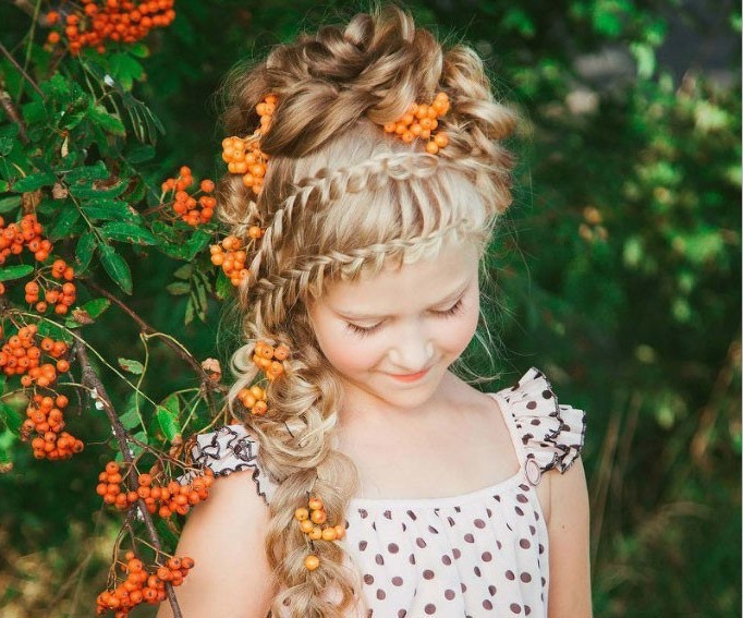 polka dot printed summer dress, worn by a smiling blonde girl, with two rows of braids, woven into one long plaid, kids hairstyles, messy curly bun, on top of her head