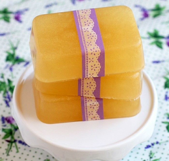 bars of orange soap, decorated with white and purple, lace like paper ribbon, handmade gifts, placed on a white dish