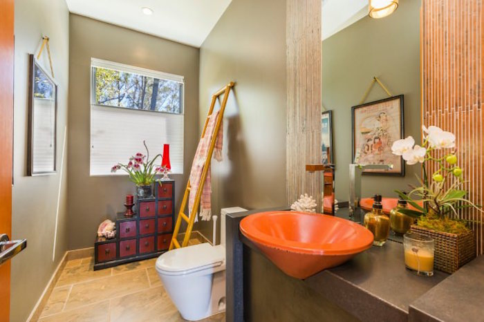 cherry red and black, east asian-style cupboard, inside a bathroom with beige walls and floor, containing a white toilet seat, and bright orange sink