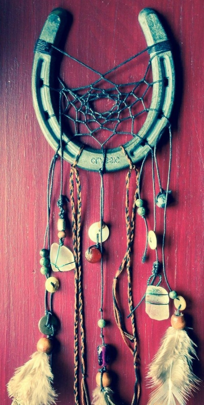 horseshoe in green, transformed into a diy dreamcatcher, with a dark teal net, and small beads, feathers and stones, tied on multicolored strings
