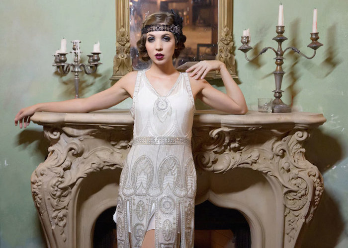 white gatsby themed dress, with silver at deco embroidery, on a woman with 1920s flapper make up, and brunette hair styled in a mock-bob
