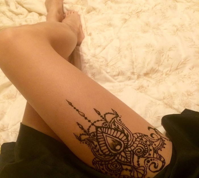 upper thigh cute henna tattoo, on the leg of a woman, dressed in a black skirt, lying on a cream duvet