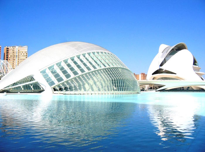 cultural center in valencia spain, with an oval shape and metal bar-like structures, post modernity, built on a blue pool of water