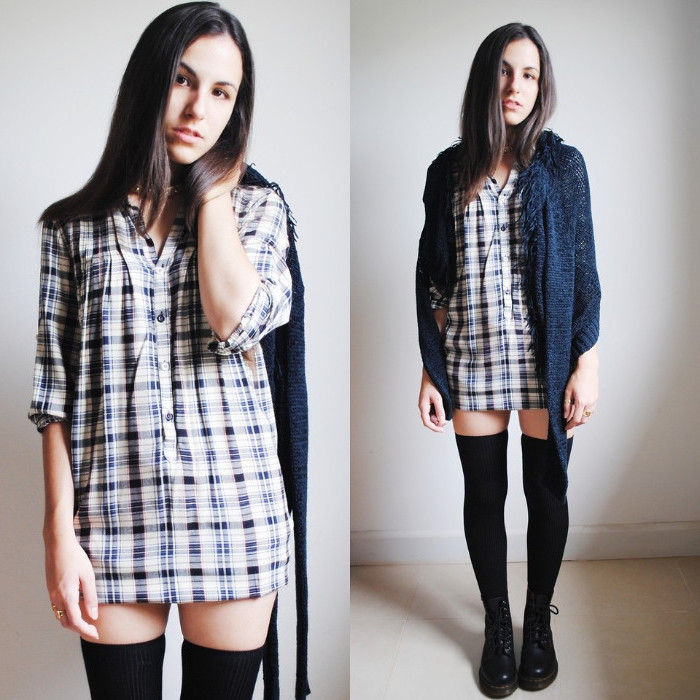 brunette young woman, wearing a white and blue checkered shirt, black over-the-knee socks, black combat boots, and a blue cardigan