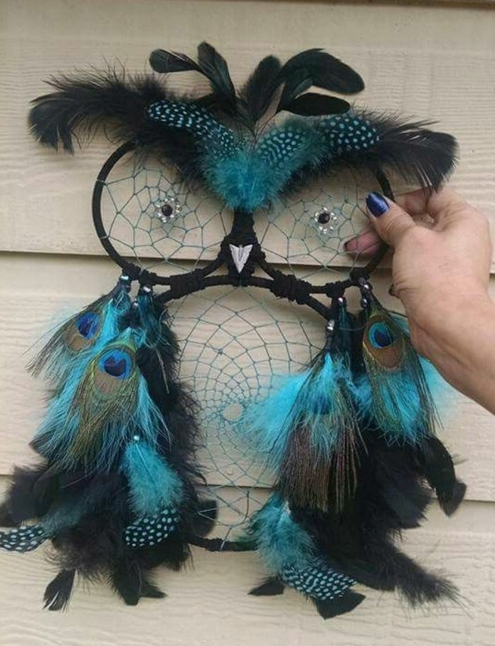 dreamcatcher designs, owl-shaped dream catcher in black, decorated with turquoise and black, spotted and peacock feathers, and held by a hand