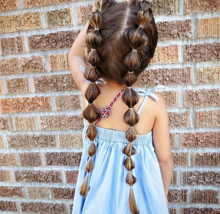 many rubber hairbands, decorating the two long pigtails, of a small child, in a pale blue summer dress