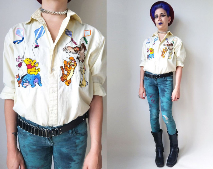 winnie-the-pooh characters embroidered on a pale yellow shirt, worn by a woman with violet hair, wearing violet lipstick, 90s halloween costumes, black boots and skinny jeans, decorated with paint, 90s retro jumper outfit