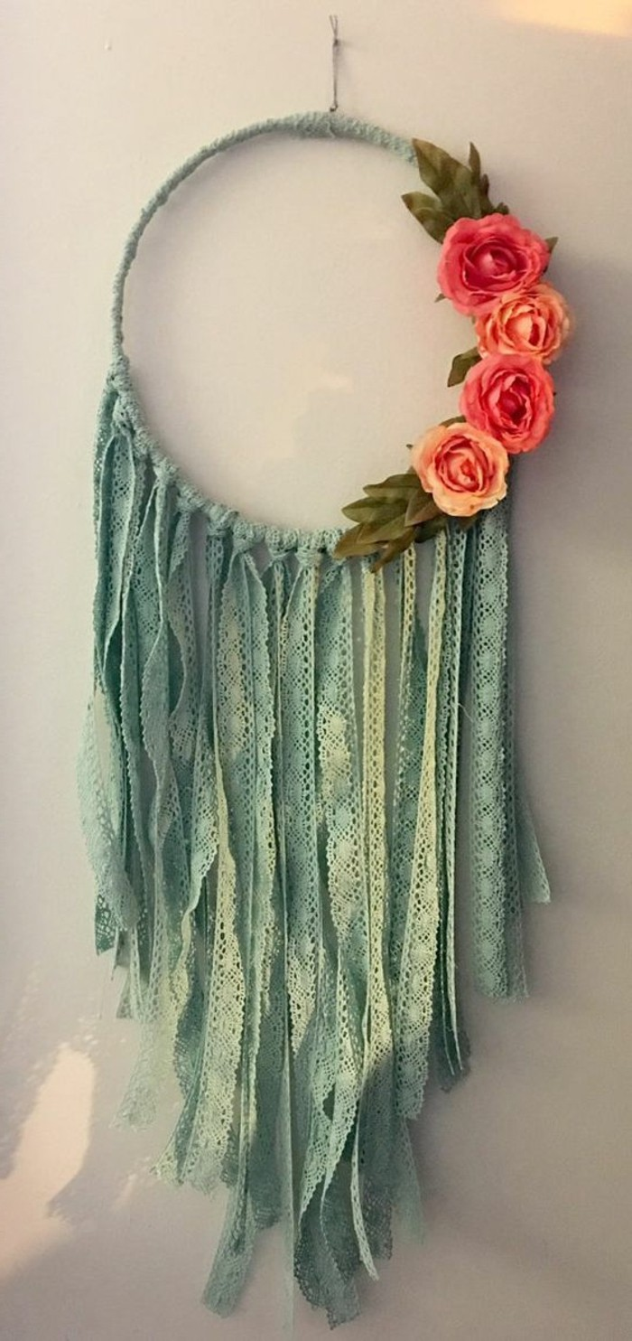 hoop wrapped in pale teal leather rope, decorated with many strips of teal lace, big dream catchers, four orange faux roses on its left side