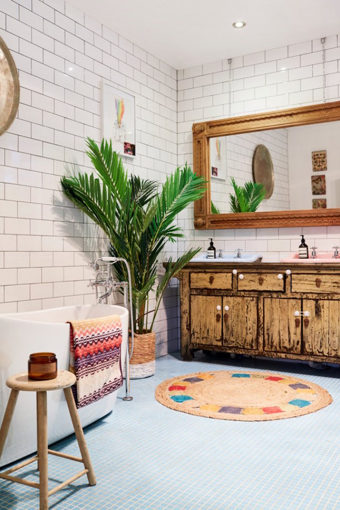 shabby chic cupboard in pale brown, a large mirror in a wooden frame, and a potted palm tree, bathroom decorating ideas on a budget, round multicolored rug