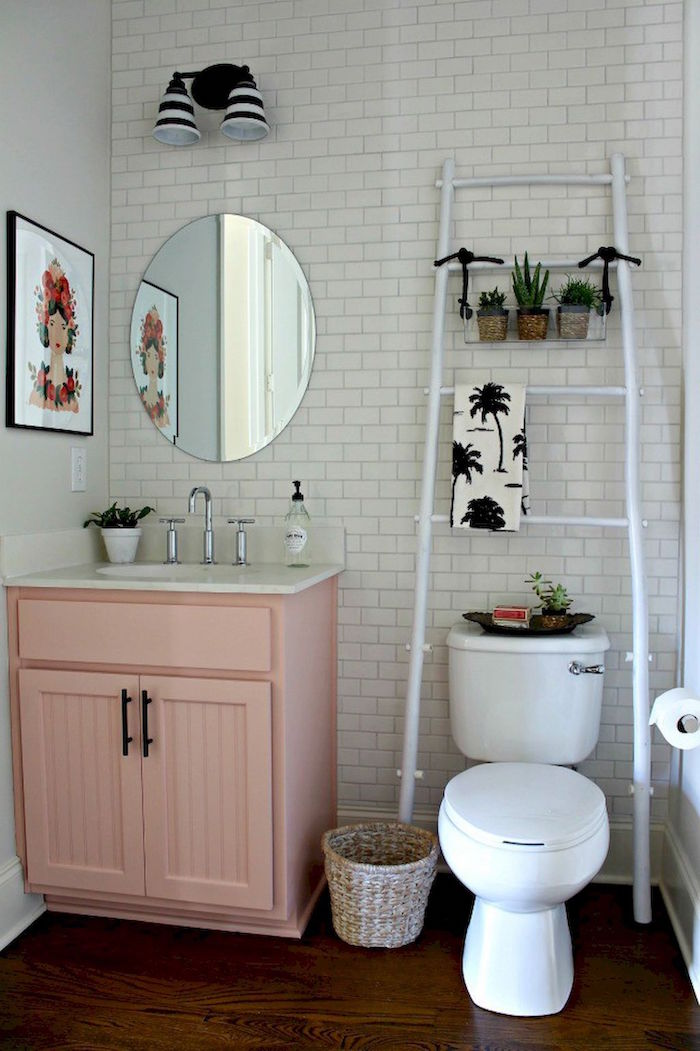 decorative white ladder, with three small potted plants, in a room wit white subway tiles, pale pastel pink cupboard with an inbuilt sink, and a white toilet, small bathroom décor, oval mirror and framed artwork