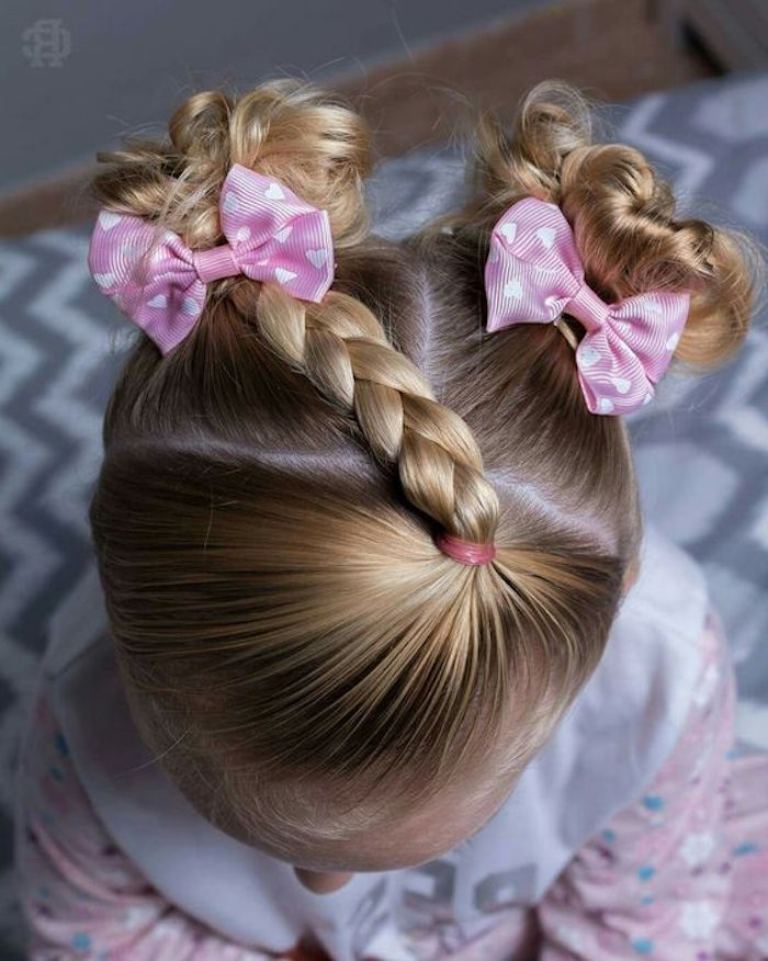 side-braid and two small, curled pigtails with bows, cute hairstyles, on the head of a small girl