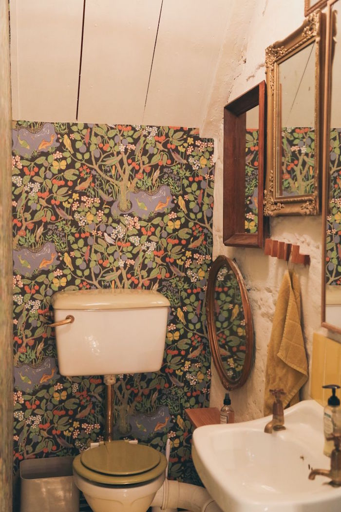 wallpaper in green, depicting trees and birds flowers and fruit, in a small room, with a vintage toilet bowl, a white stink, and several mirrors in wooden frames, small bathroom decoration ideas, floor to ceiling cupboard with white wooden boards