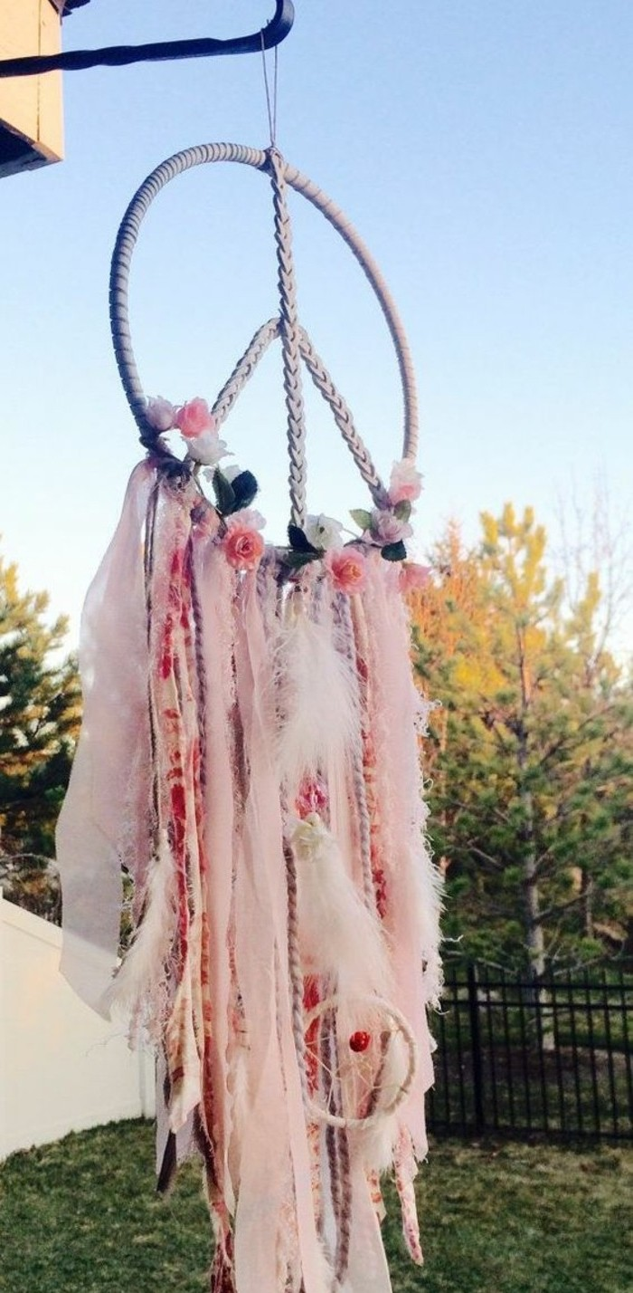 assortment of fabric strips, and ribbons in different shades of pink, tied to a large dream catcher, shaped like a peace sign