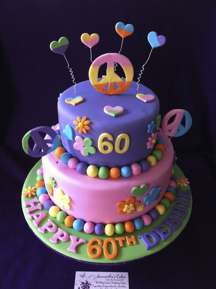 hearts and flowers, peace signs and multicolored details, decorating a two-layered cake, happy 60th birthday, hippie inspired party