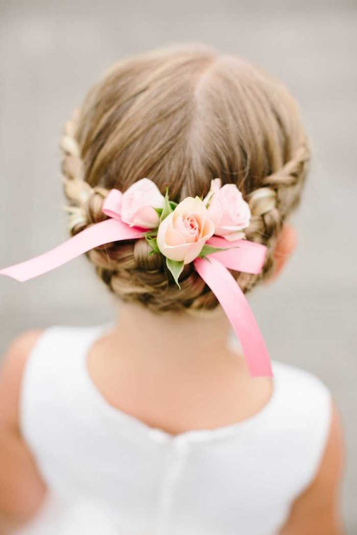 bridesmaid or flower girl's hairstyle, seen from the back, dark blonde hair, with a braided up-do, decorated with pale, peach-colored roses, and a pink ribbon