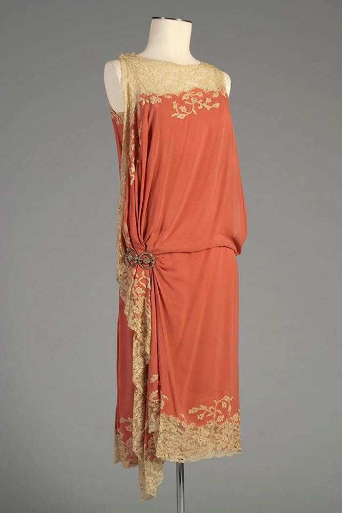 gatsby themed dress in peach pink, with cream-colored vintage lace trims, around its collar and hem, fastened with a metal brooches at the side