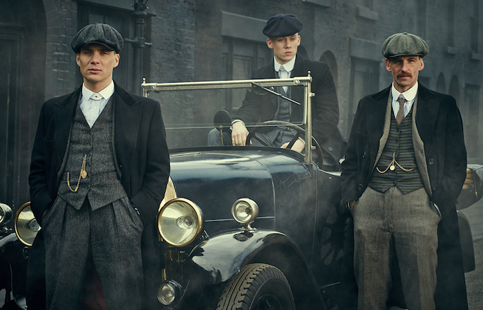 cillian murphy and two of his co-stars, dressed as 1920s british gangsters, standing in or next to an antique car, 20s mens fashion