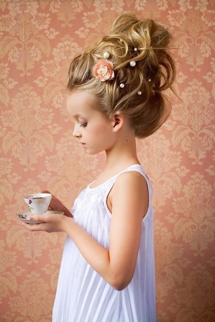 voluminous blonde up-do, decorated with pearl-like details, and a peach floral motif, worn by a small child, holding a teacup, in a formal, white sleeveless dress