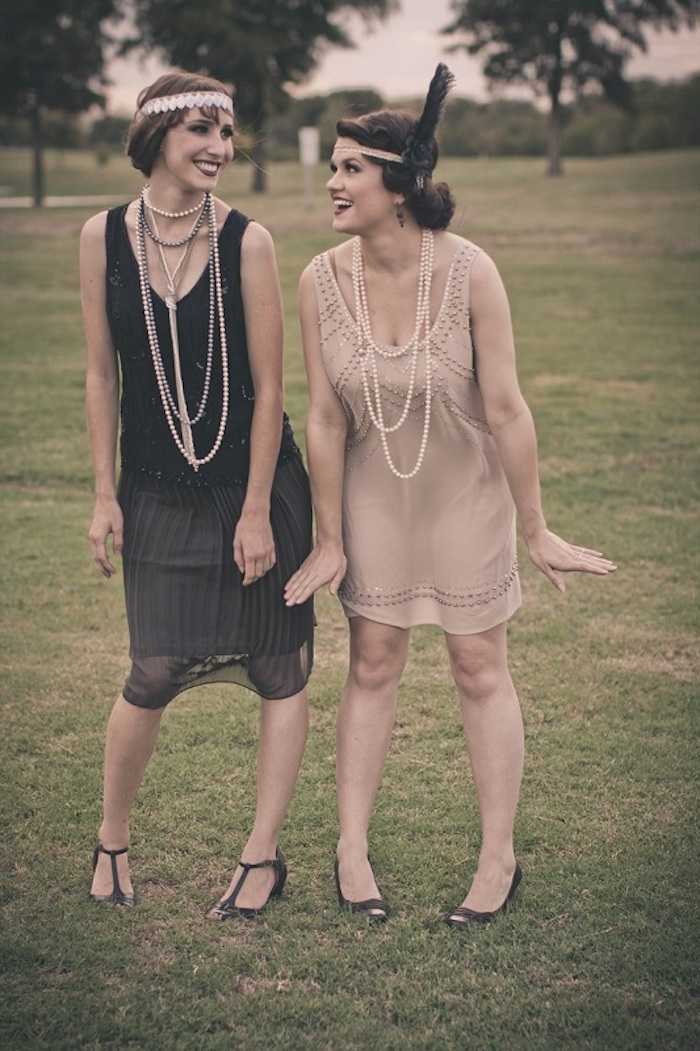 smiling women posing for a photo, one dressed in a midi, black roaring 20s dress, with t-bar shoes, a headband and long pearl necklaces, the other is in a similar dress in pale pink