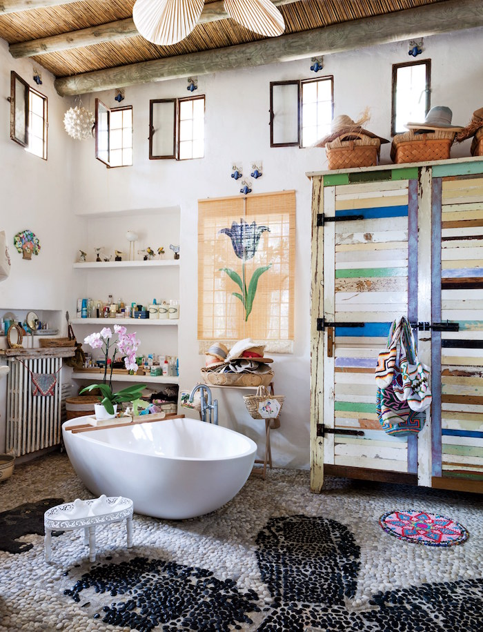 nice bathrooms, spacious room with a high ceiling, and a pebbled floor, in pale grey and black, with a white oval bathtub, and multicolored, tall shabby chic cupboards