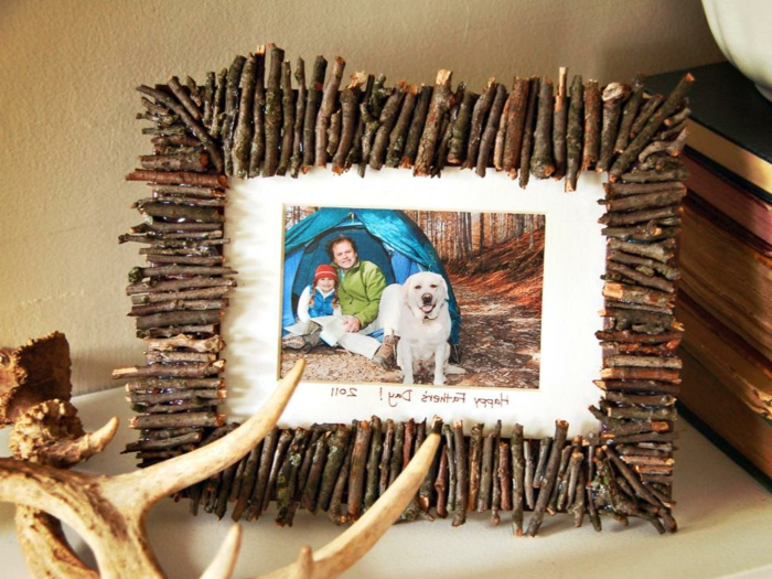 frame made from small twigs, containing a photo, of a father, his daughter and their dog, in front of a tent