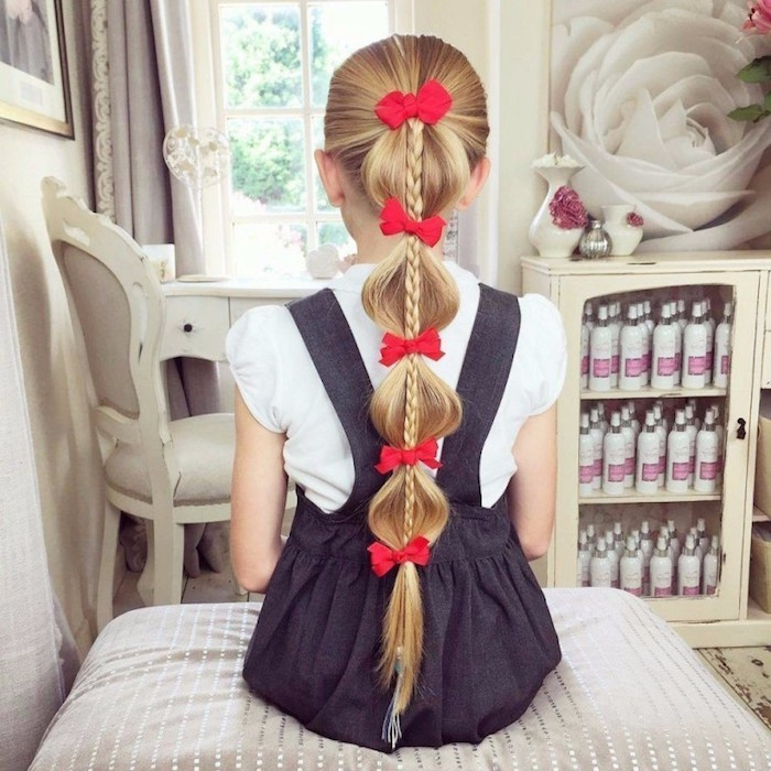 five small red bows, decorating the long, blonde hair of a young girl, with a weist-long braid, simple hairstyles, dark grey pinafore dress, with a white short-sleeved shirt