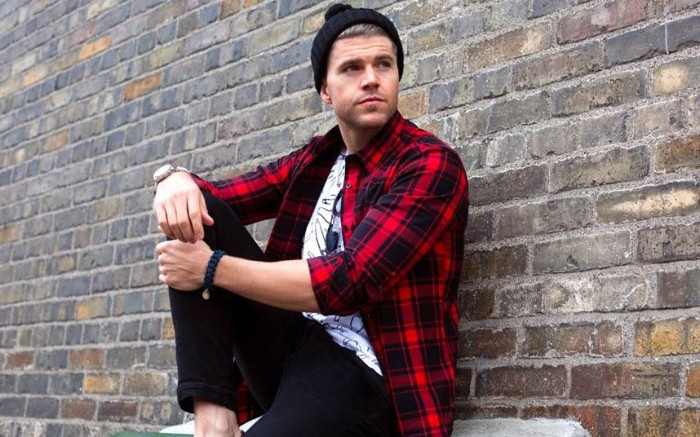 sitting man with black beanie hat, wearing an unbuttoned, red and black plaid shirt, and a white tee with black print, skinny black trousers