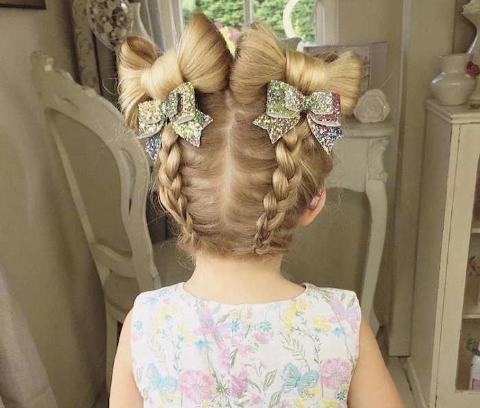 sparkly multicolored bow-shaped hair ornaments, decorating the blonde hair, of a small girl, two symmetrical braids, with bow-motifs