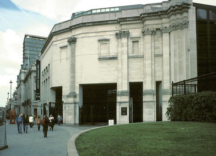 off-white and grey concrete building, with filled-in windows, and roman-like columns, sainsbury wing of the national gallery in london, next to a busy street