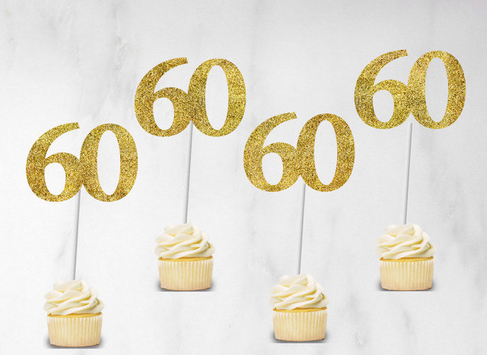 glittering gold toppers, shaped like the number 60, decorating four plain vanilla cupcakes, placed on a white background