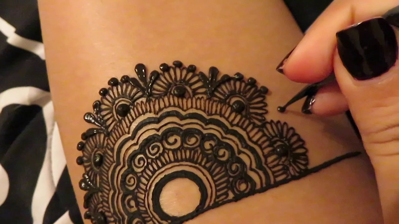 freshly made dark henna temporary tattoo, with circles and flourishes, henna meaning, hand adding a black dot, using a cone