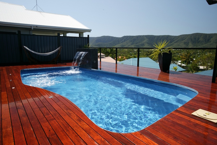 reddish-brown patio, with lacquer coated planks, containing a pool with irregular shape, small backyard pool ideas, black wall with a hammock