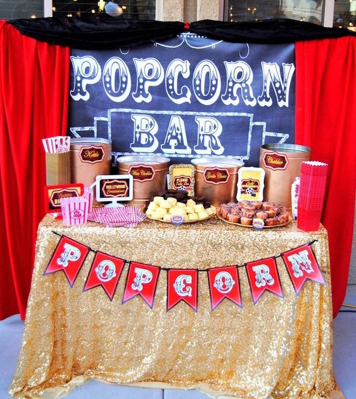 curtains in red and black, around a table with a sign, reading popcorn bar, 60th birthday decorations, a selection of various snack, gold lame tablecloth, and red flags garland