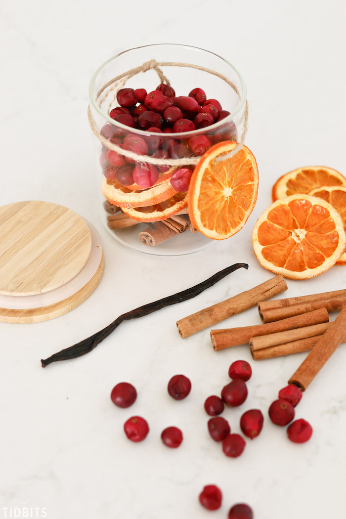 potpourri in a glass jar, made with dried orange slices and cranberries, cinnamon and vanilla sticks, diy christmas gifts